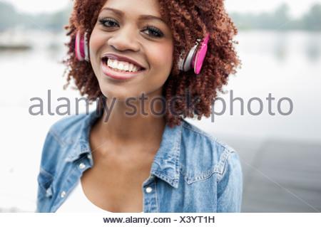 Portrait of young woman wearing headphones - Stock Photo