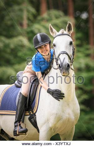 Lusitano. Rider fondling grey horse Austria - Stock Photo