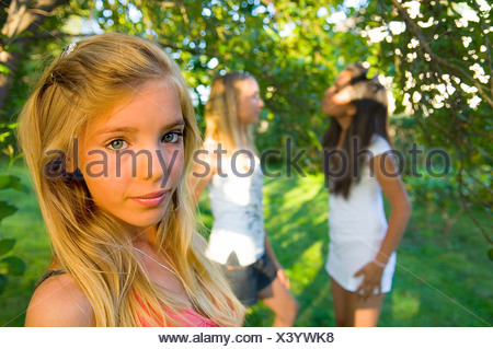 Close-up portrait of a blonde teenage girl with blurred female friends in the background - Stock Photo