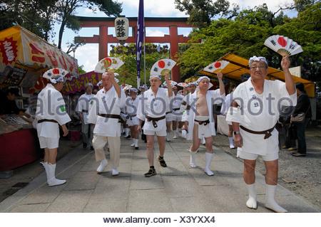 Handles of the shrines being carried accompanied by waving fans, Matsuri Shrine Festival of the Matsuo Taisha Shrine, Shinto - Stock Photo