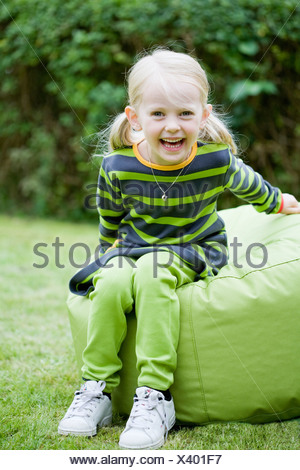 Girl sitting on bean bag on garden - Stock Photo