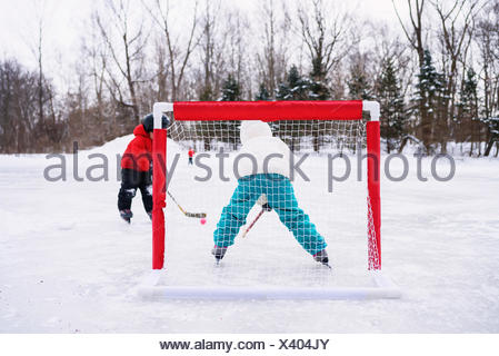 Two children playing ice hockey on frozen lake - Stock Photo
