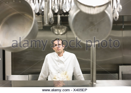 Dirty chef leaning against stove - Stock Photo