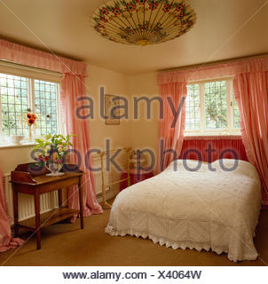 Crocheted cotton bedspread on bed in early eighties bedroom with pink curtains with a parasol used as a lampshade - Stock Photo