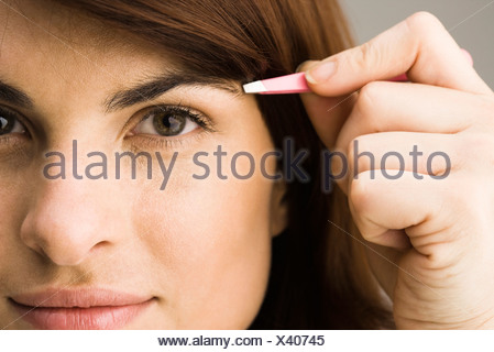 Young woman tweezing eyebrows - Stock Photo