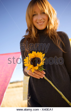 Female holds a sun flower and smiles. - Stock Photo