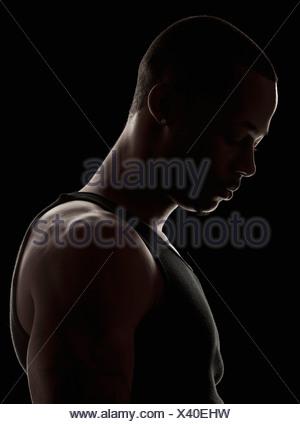 Studio shot of muscular young man wearing tank top - Stock Photo