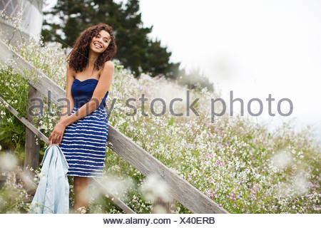 Young woman laughing by meadow - Stock Photo