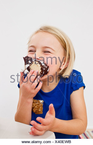 Studio portrait of young girl eating chocolate marshmallow - Stock Photo