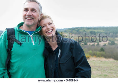 Hiking couple in rural landscape - Stock Photo