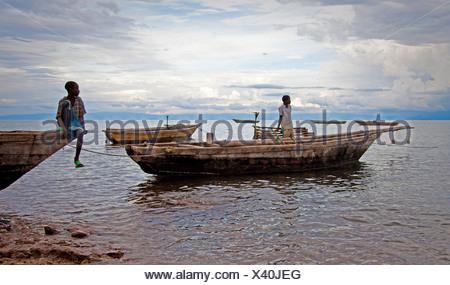 two boys on fishing boats at Lake Tanganyika, Burundi, Makamba, Mvugo, Nyanza Lac - Stock Photo