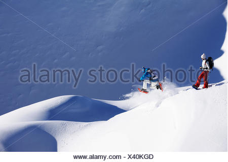 man and woman with snow shoes on a snow-covered slope, France - Stock Photo