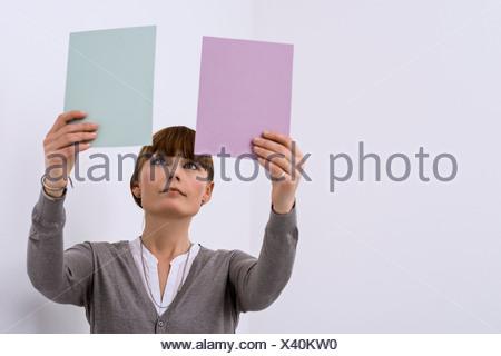 Female designer comparing color samples - Stock Photo