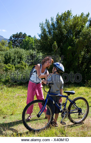 Boy  with bicycle, mother adjusting son's helmet - Stock Photo