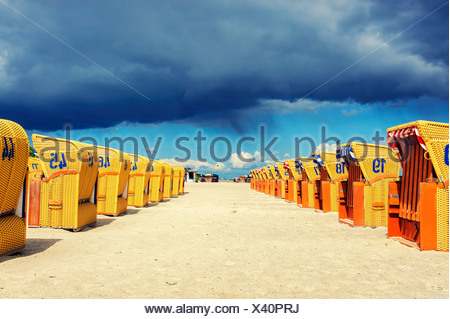 Two rows of yellow roofed wicker beach chairs in the sunshine, dark rain clouds at the back, Mecklenburg-Western Pomerania - Stock Photo