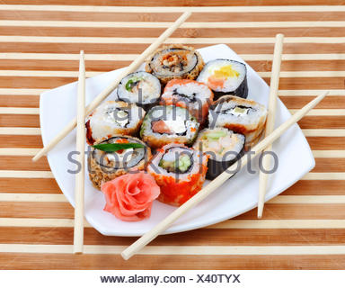 Sushi rolls on the plate with chopsticks - Stock Photo
