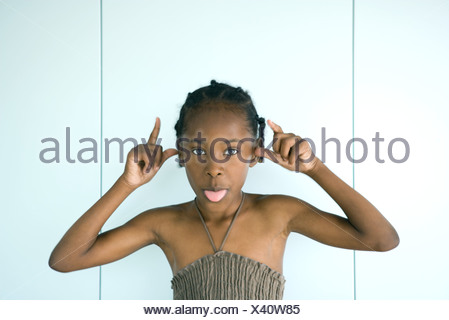 Little girl sticking tongue out at camera, arms raised, portrait - Stock Photo