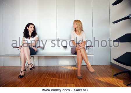 Two young women in waiting room - Stock Photo
