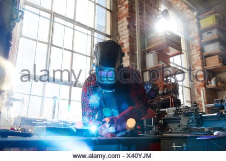 Welder welding with welding mask and torch in workshop - Stock Photo