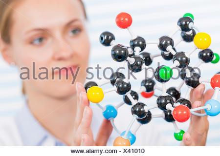 MODEL RELEASED. Female chemist examining molecular model. - Stock Photo