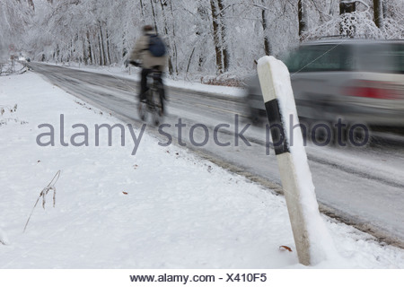Cyclist being overtaken on a snowy country road in winter, Hesse, Germany, Europe - Stock Photo