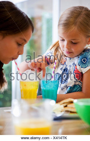 Close up of two sisters blowing bubbles through straws at breakfast bar - Stock Photo
