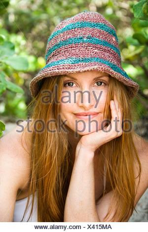 Portrait of pretty redheaded woman wearing hat - Stock Photo