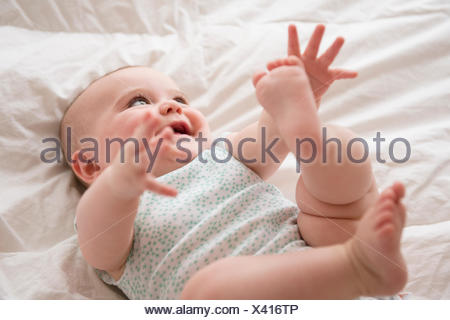 Baby girl (12-17 months) lying down with arms and legs up - Stock Photo