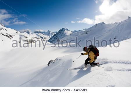 Man telemark skis down hill in Canada backcountry near Alaska Canada border - Stock Photo