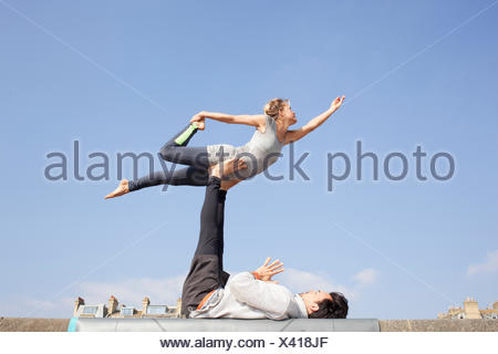 Man and woman practicing acrobatic yoga on wall