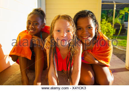 Portrait of three girls wrapped in towel on porch - Stock Photo