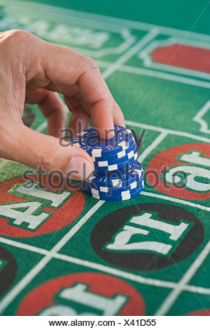 Man placing gambling chips on roulette table - Stock Photo
