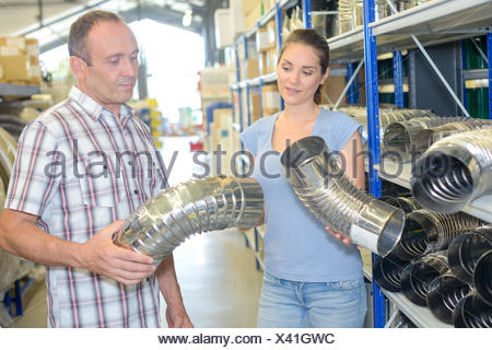Man and lady looking at chimney flues - Stock Photo