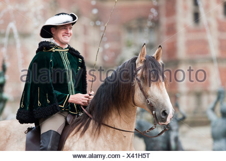 Frederiksborger with rider in historic costume in front of Frederiksborg Palace, Danmark - Stock Photo