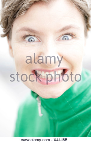 Close-up, woman wearing a green jacket showing her teeth - Stock Photo