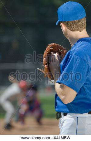 Baseball pitcher preparing to pitch ball - Stock Photo