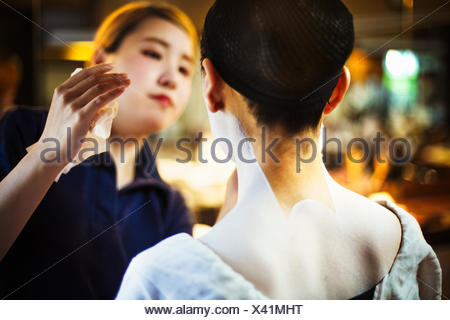 A modern geisha or maiko woman being made up in traditional fashion, with white makeup on her neck and shoulders. - Stock Photo