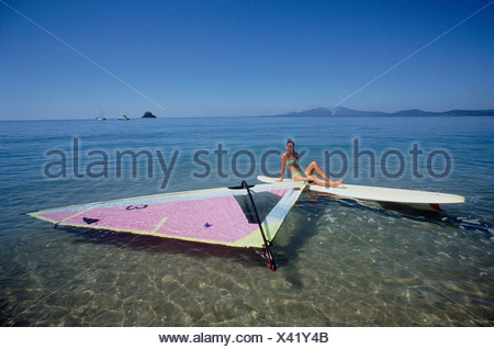 Young woman resting on sailboard floating on water. Dunk Island. Queensland. Australia. - Stock Photo