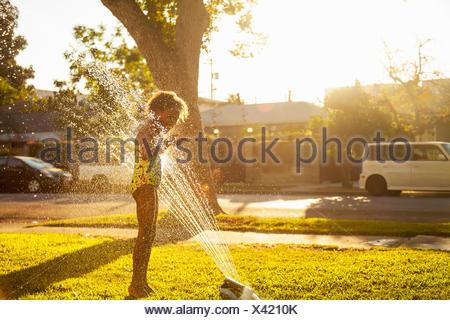 Girl standing in garden sprinkler - Stock Photo