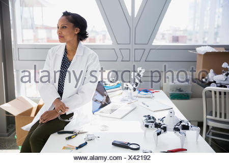 Pensive engineer at desk with robots - Stock Photo