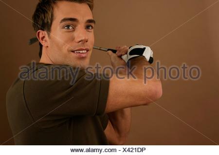 A golf player swinging golf club - Stock Photo