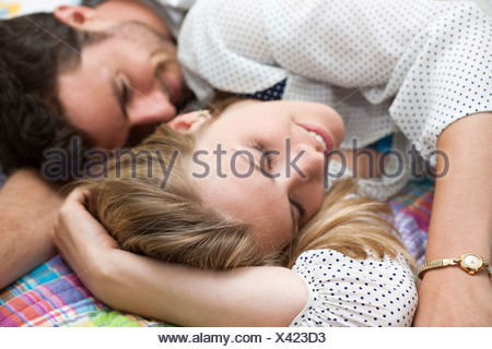 Close up of couple relaxing on bed - Stock Photo
