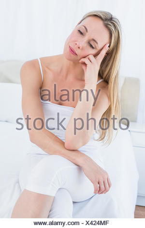 Unhappy blonde suffering from head pain - Stock Photo