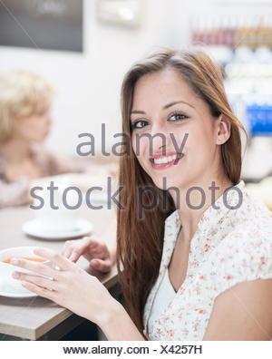 Portrait of beautiful young woman having coffee at table in cafe - Stock Photo