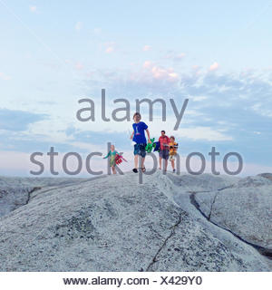 Father with three children walking across rocks, Norway - Stock Photo