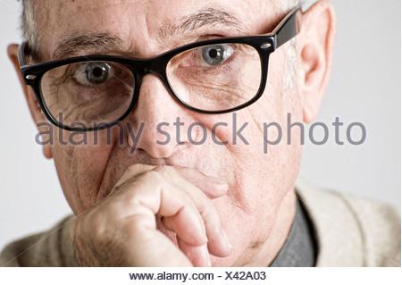 Portrait of senior man, hand on mouth - Stock Photo