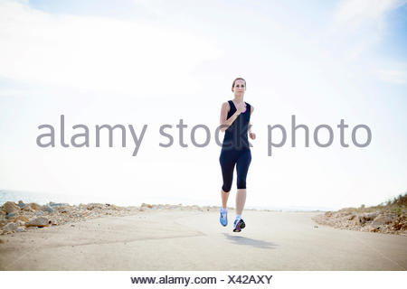 Young woman running on waterfront path - Stock Photo