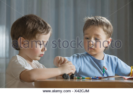 young boys playing with shape game - Stock Photo