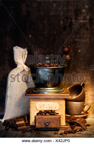 Stiill life with Antique coffee grinder, burlap sack, coffee cups and chocolate on rustic table - Stock Photo