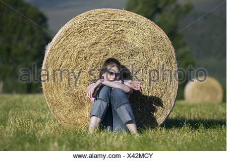 Young girl relaxing against hay bale in summer, United Kingdom, Scotland, Cairngorms National Park - Stock Photo